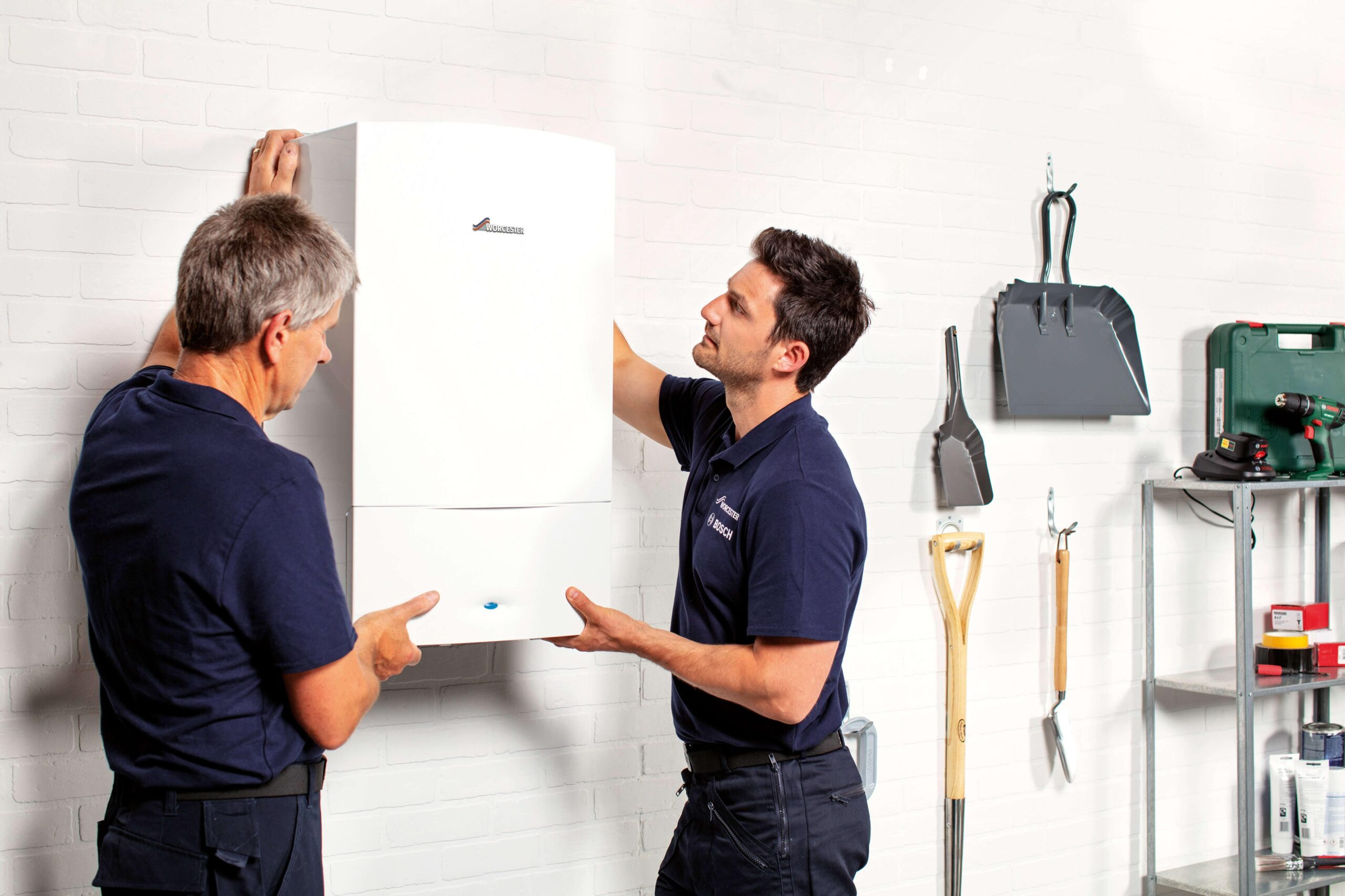 Heating Engineer in Plymouth: Image of two men installing a Worcester-Bosch boiler.