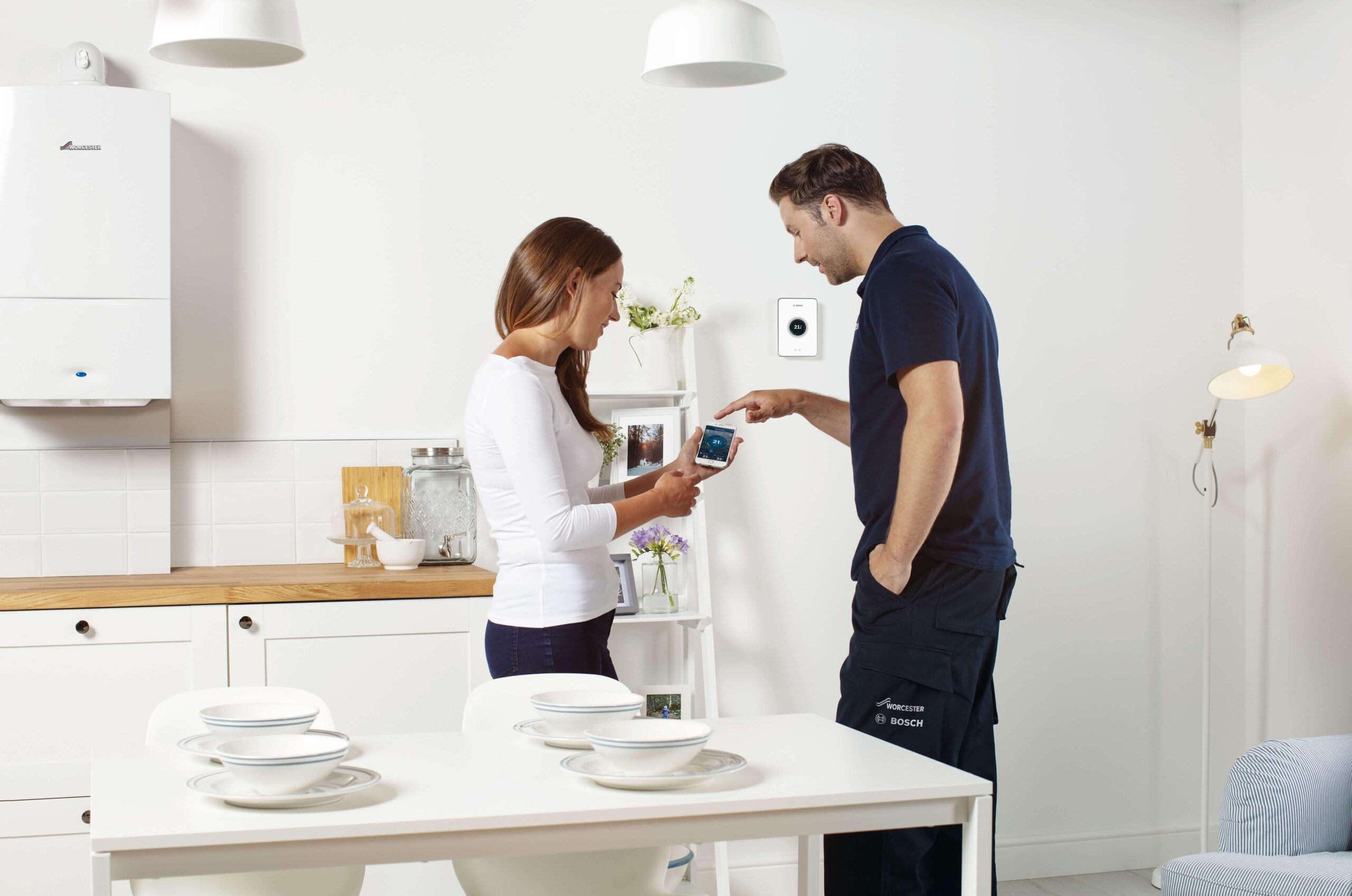 Heating Engineer in Totnes: Image of a heating engineer showing a customer how to programme a boiler via a smart phone.