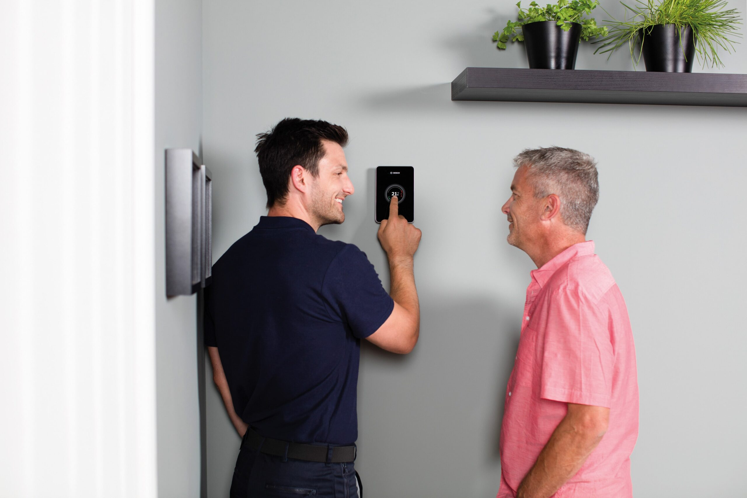 Heating Engineer in Plympton: Image of a heating engineer showing a customer how to use a thermostat.