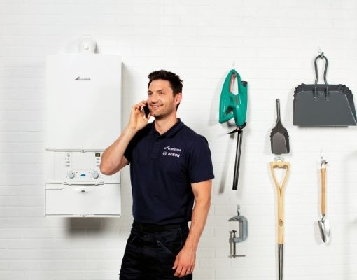 Heating Engineer in Torpoint: Image of a heating engineer on the phone, stood next to a boiler.