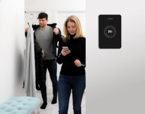 Heating Engineer in Torpoint: Image of a woman stood next to a smart thermostat.